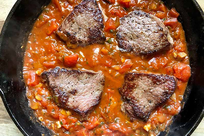 Horizontal image of four portions of seared meat on top of a red stew in a skillet.