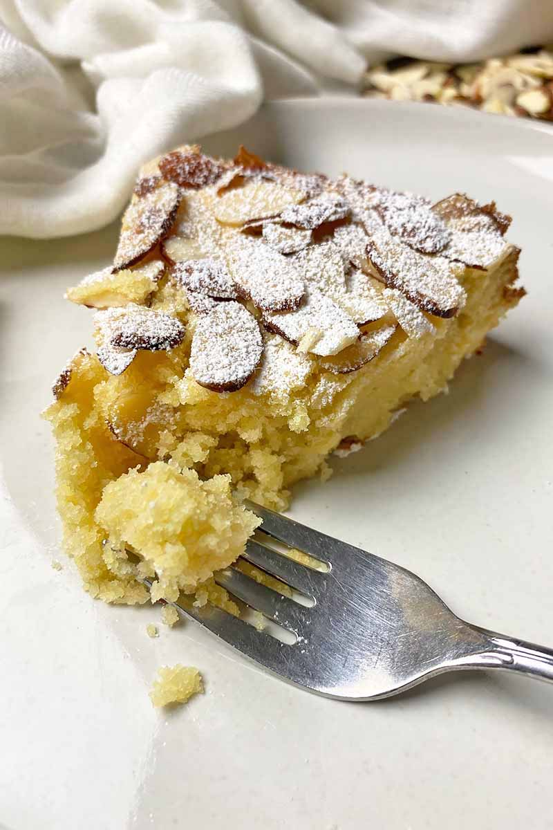 Vertical image of a fork cutting into a moist yellow cake garnished with nuts and powdered sugar on a white plate next to a white towel.