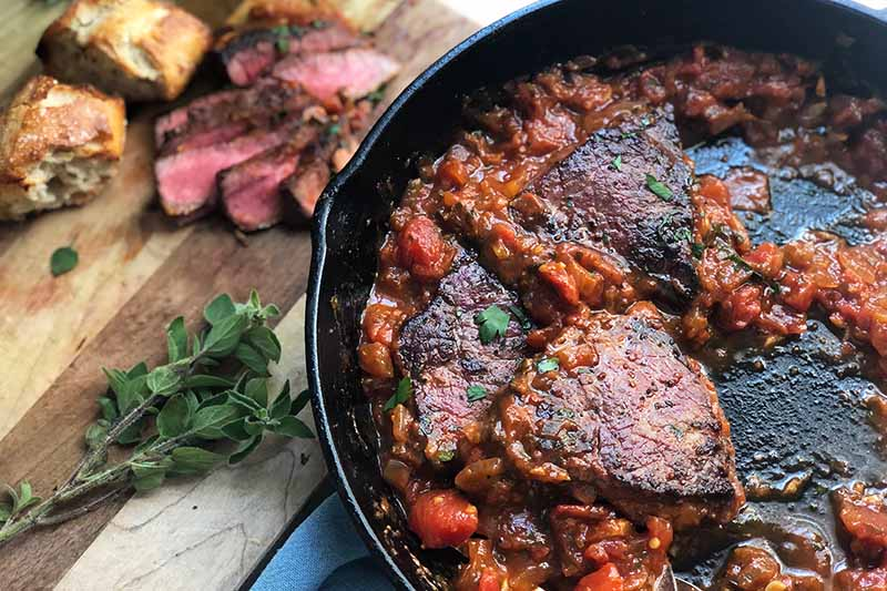 Horizontal image of a red stew with portions of seared meat, next to sliced meat, herbs, and bread on a wooden cutting board.