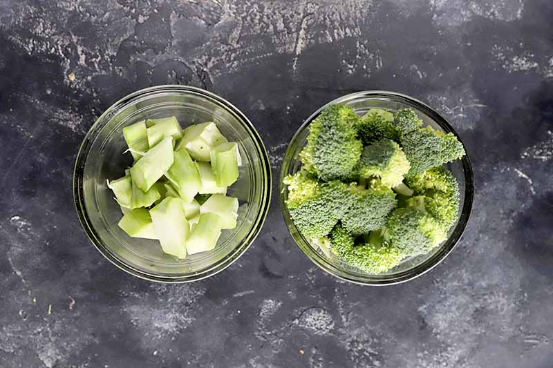 Horizontal image of the chopped stems and florets of a green vegetable in bowls.