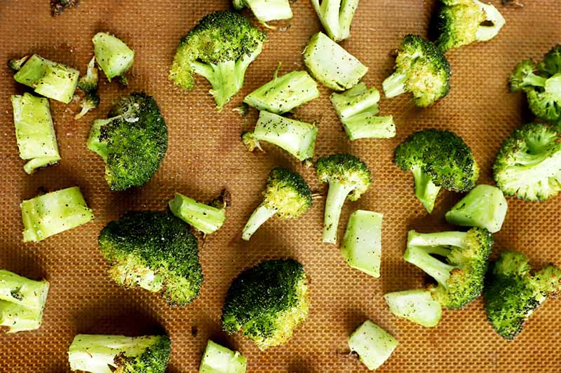 Horizontal image of roasted green stalks and florets on a silicone mat.
