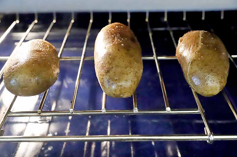 Horizontal image of three whole spuds directly on an oven rack.