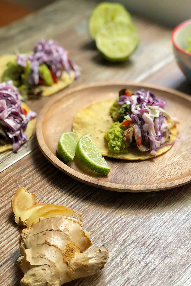 Vertical image of corn tortillas topped with cooked vegetables and red cabbage slaw next to limes, ginger, and smashed avocados on a wooden table.