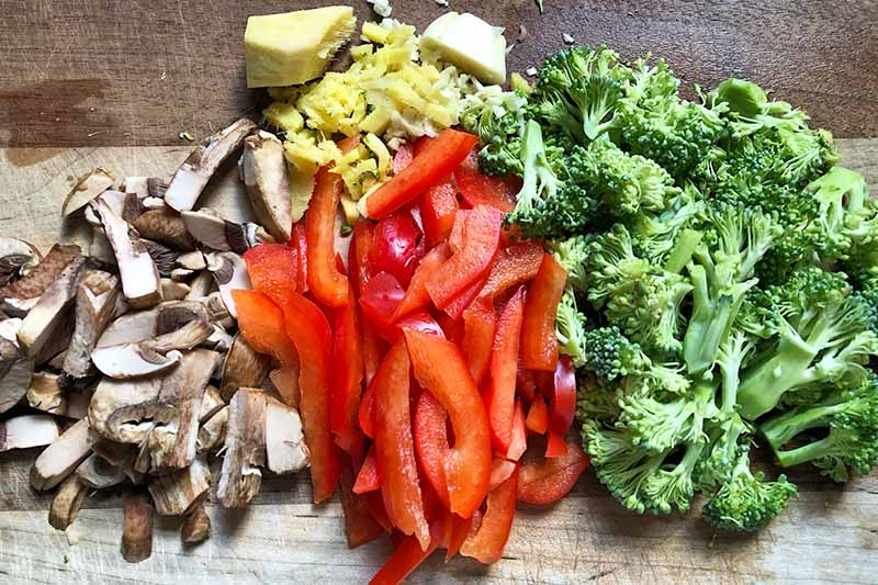 Horizontal image of sliced mushrooms, broccoli, and peppers and minced garlic and ginger.