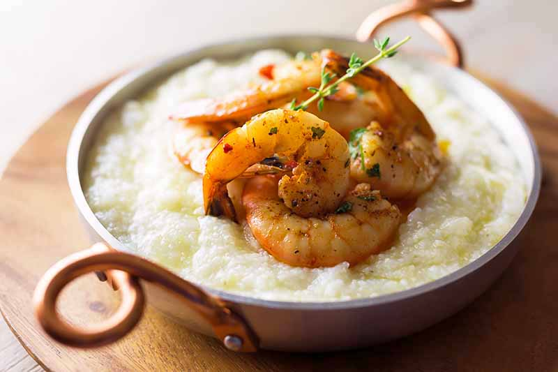 Horizontal image of a pot with shrimp and grits on a wooden platter.