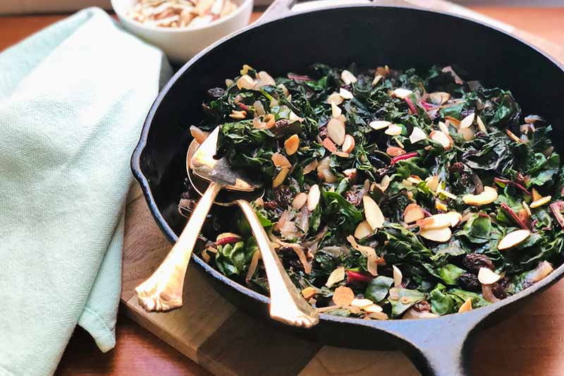 Horizontal image of a cast iron skillet filled with cooked greens mixed with onions, nuts, and raisins with serving spoons next to a blue towel.