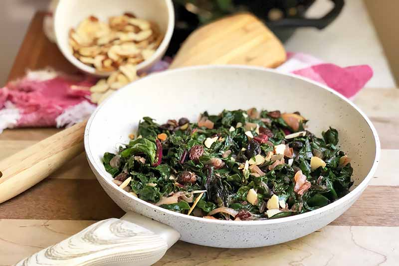 Horizontal image of a white pan with cooked greens mixed with onions, raisins, and nuts next to a wooden spoon and a bowl of nuts.