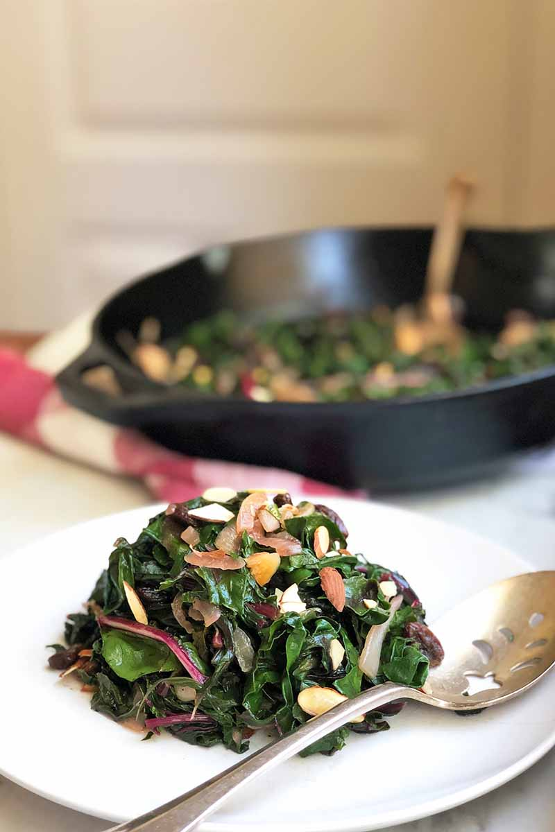 Vertical image of a white plate and a cast iron skillet filled with cooked greens, onions, raisins, and nuts.