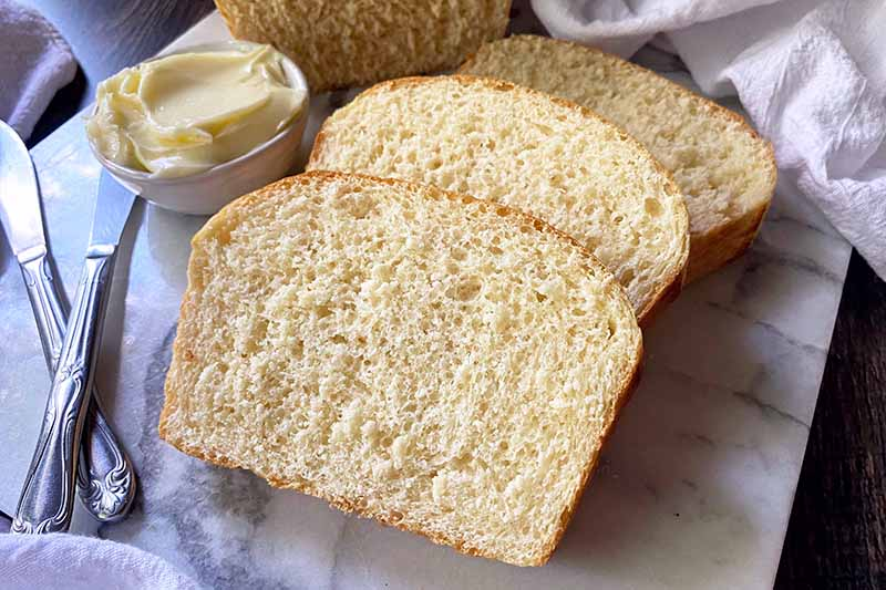Horizontal image of slices of bread on a white surface next to knives and butter.