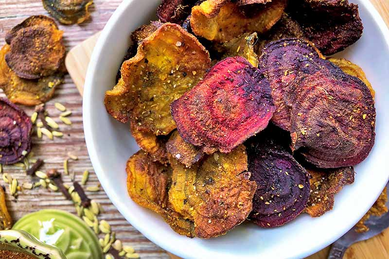 Horizontal close-up image of a white bowl filled with brightly colored and baked thinly sliced beets and parsnips.