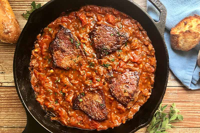 Horizontal top-down image of portions of seared meat in a red stew in a cast iron skillet.