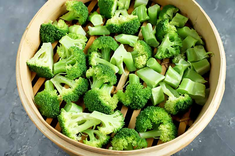 Horizontal image of cooked broccoli in a steamer basket.