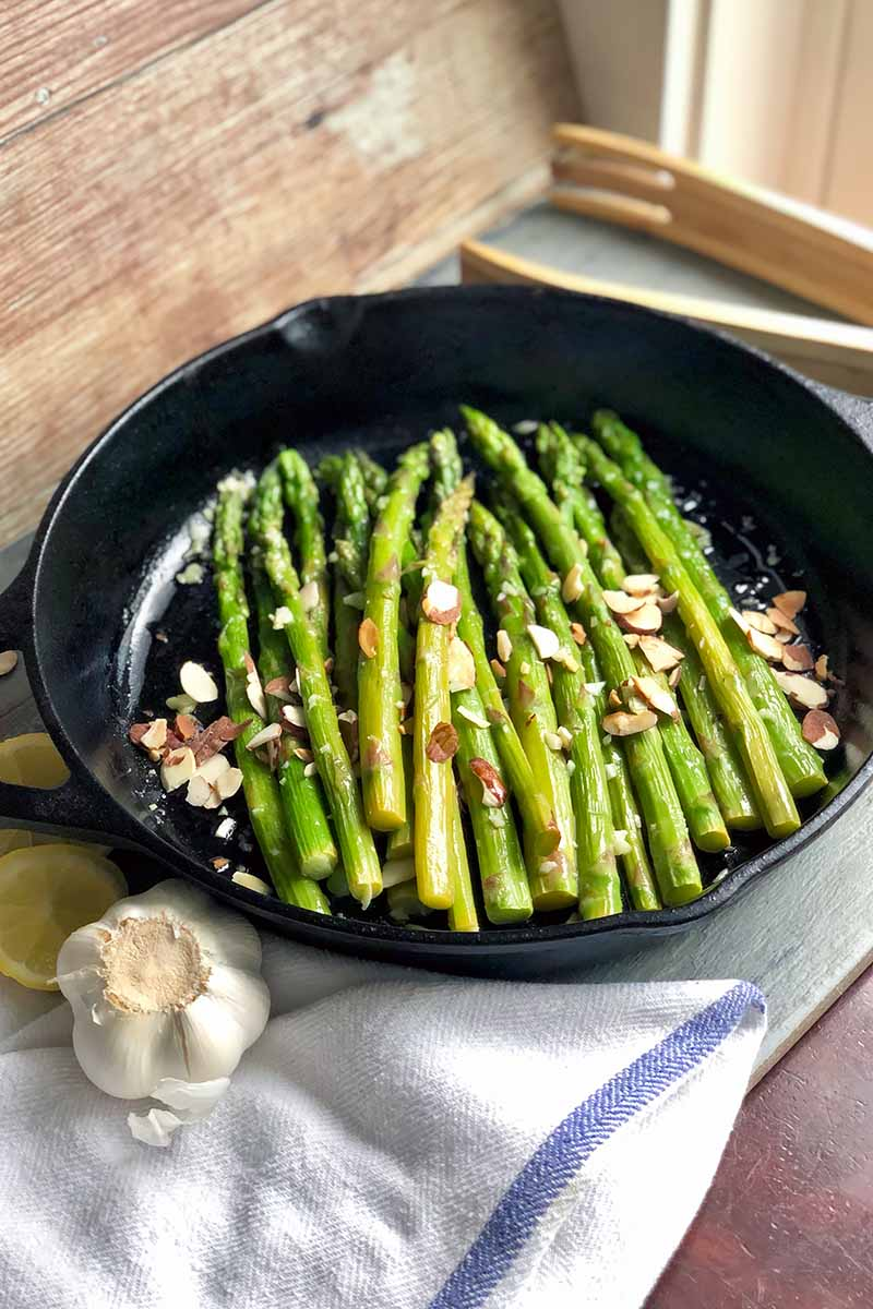 Vertical image of a cast iron skillet with cooked green vegetable stalks topped with sliced nuts next to tongs, garlic, and a white towel.