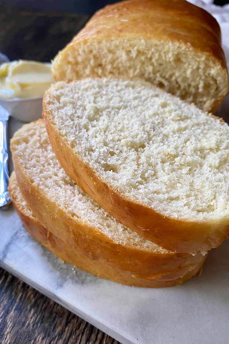 Vertical image of a stack of thick slices of bread on a white surface.