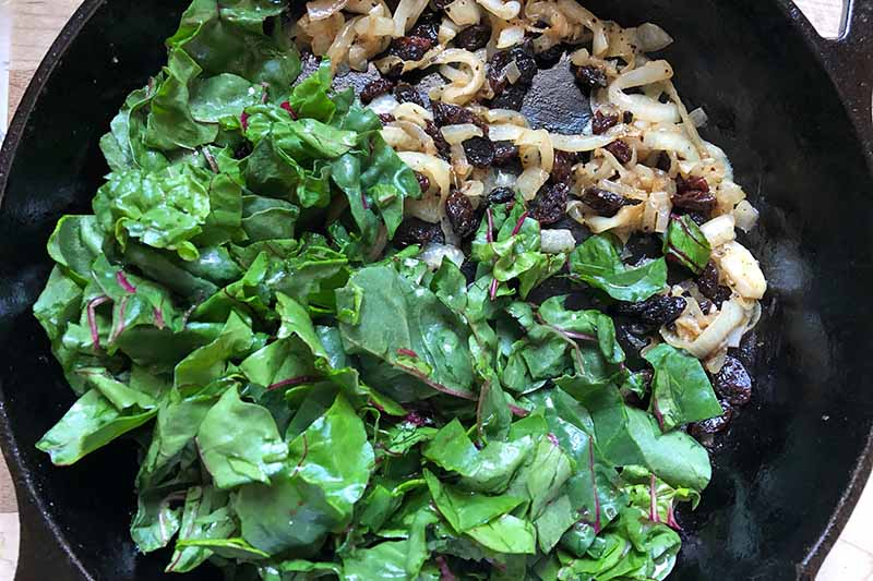Horizontal image of raw chopped greens next to raisins and onions in a cast iron skillet.