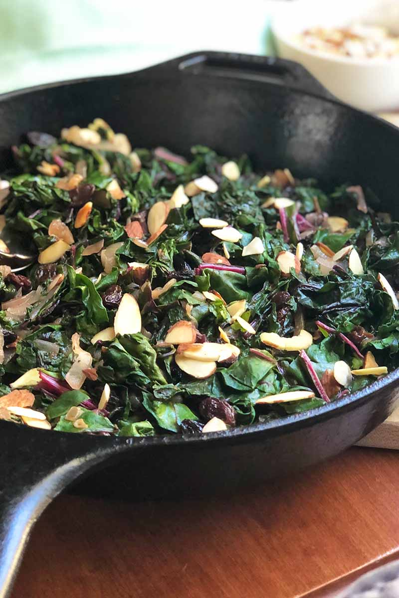 Vertical image of cooked greens with dried fruit and nuts in a cast iron skillet on a wooden table.