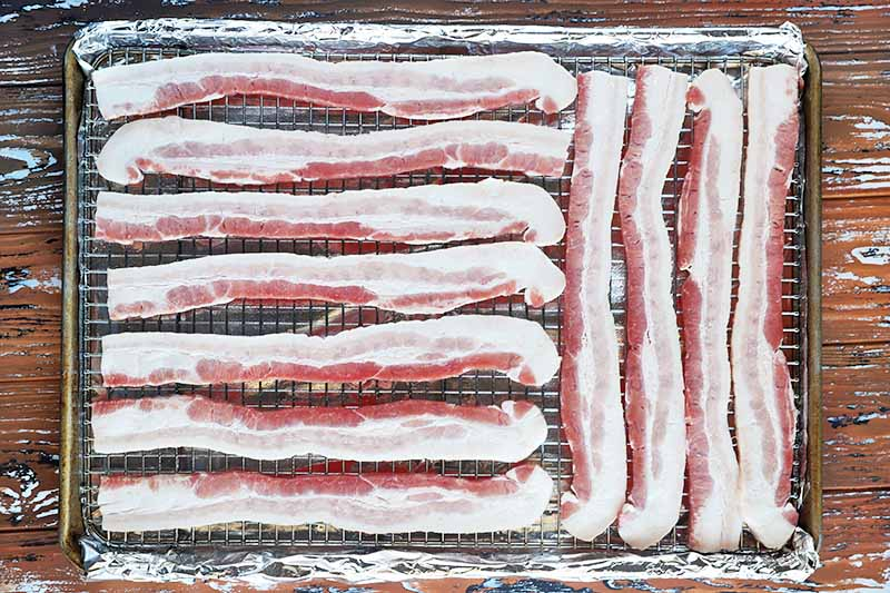 Horizontal image of slices of uncooked meat on a cooling rack over a baking sheet lined with aluminum foil.