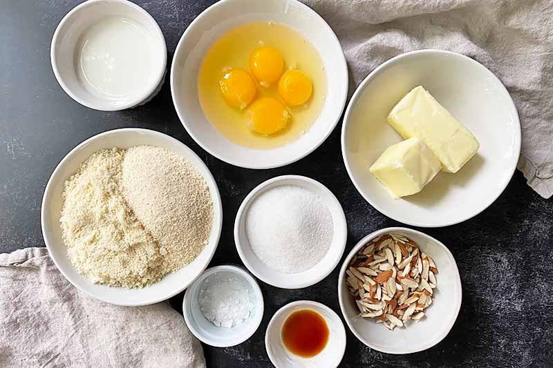 Horizontal image of assorted ingredients in white bowls on a black surface.