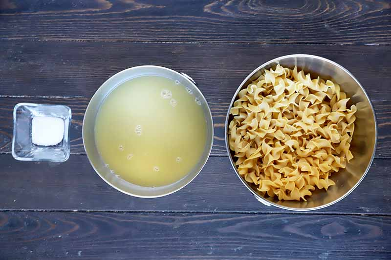 Horizontal image of a bowl of salt, a bowl of broth, and a bowl of dried pasta in a row.