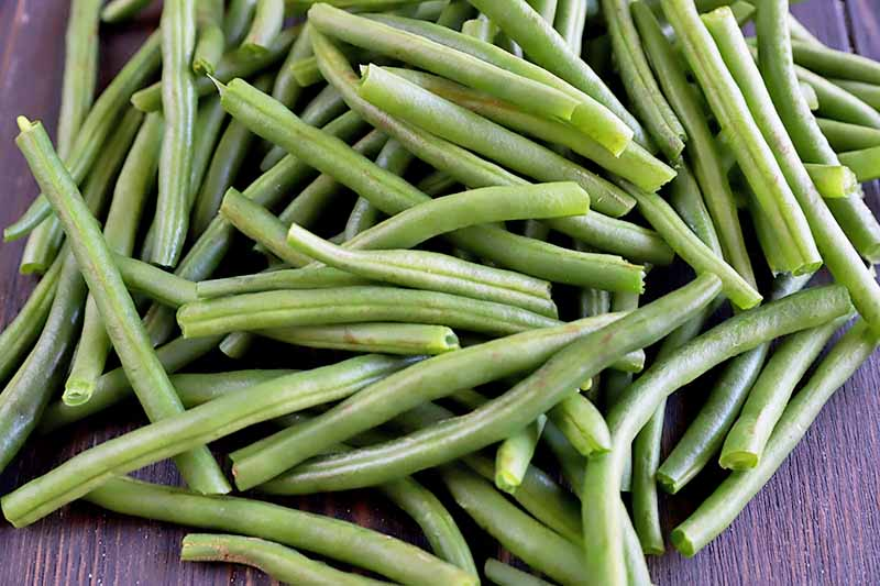 Horizontal image of raw and prepped green beans.