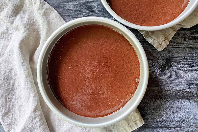 Horizontal image of brown batter in two circular metal pans.