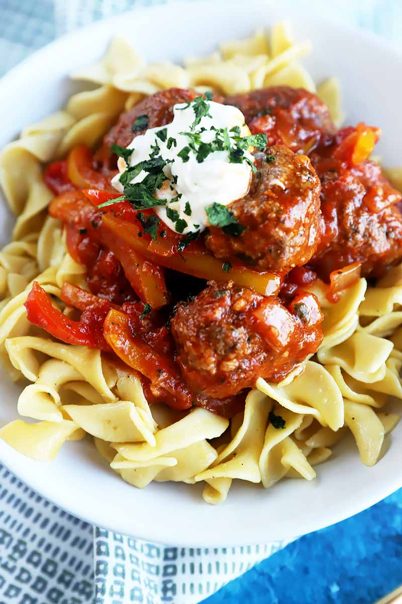Vertical image of a bowl of pasta topped with goulash and a dollop of sour cream with herbs.