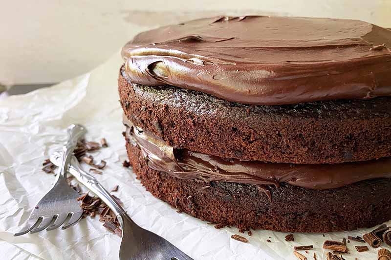 Horizontal image of a two-layered cake with cocoa frosting