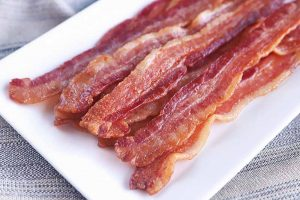 Horizontal image of a rectangular white plate with cooked strips of breakfast meat.