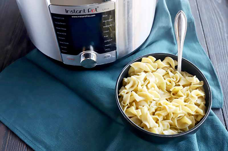 Horizontal image of a bowl of pasta with a metal spoon inserted into it on top of a blue towel next to a kitchen appliance.