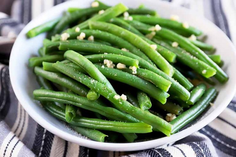 Horizontal image of seasoned cooked green beans in a white bowl on a gray and white towel.