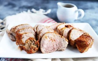 Horizontal image of slices of cooked seasoned meat on a white plate next to a cup of gravy and a towel.