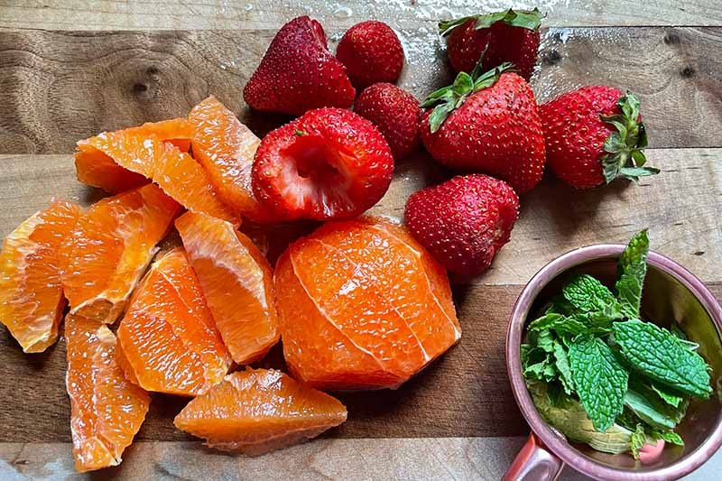 Horizontal image of slices of oranges, strawberries, and a bowl of whole mint leaves.