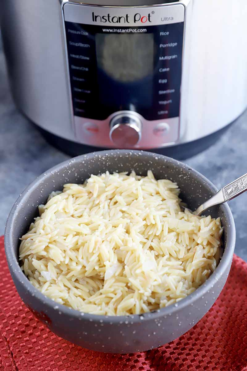 Vertical image of a bowl of pasta next to a kitchen appliance.