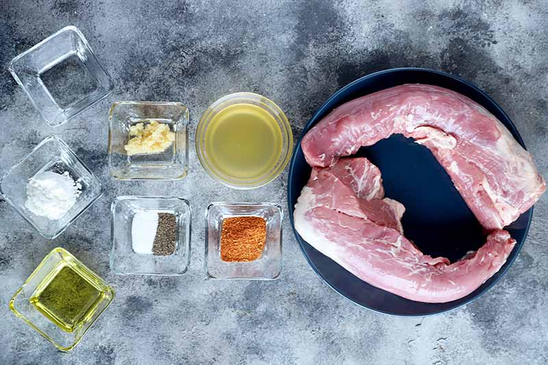 Horizontal image of a plate of raw meat next to small glass dishes of assorted measured ingredients.