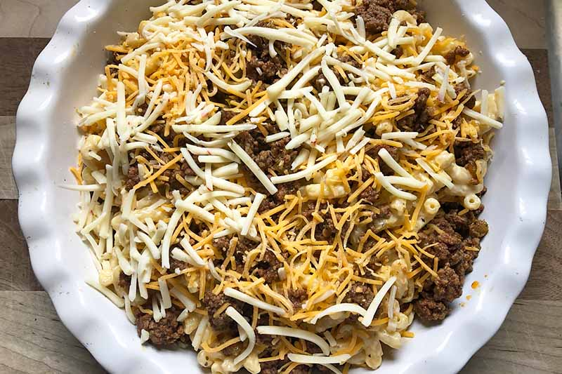 Horizontal image of ground beef, shredded cheese, and noodles in a white pie dish.