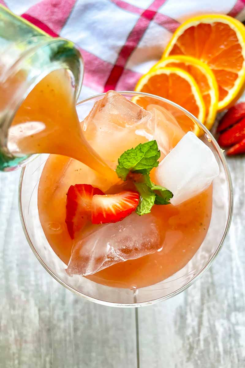 Vertical image of pouring a drink into a glass topped with ice cubes, fresh herb leaves and slices of fruit.