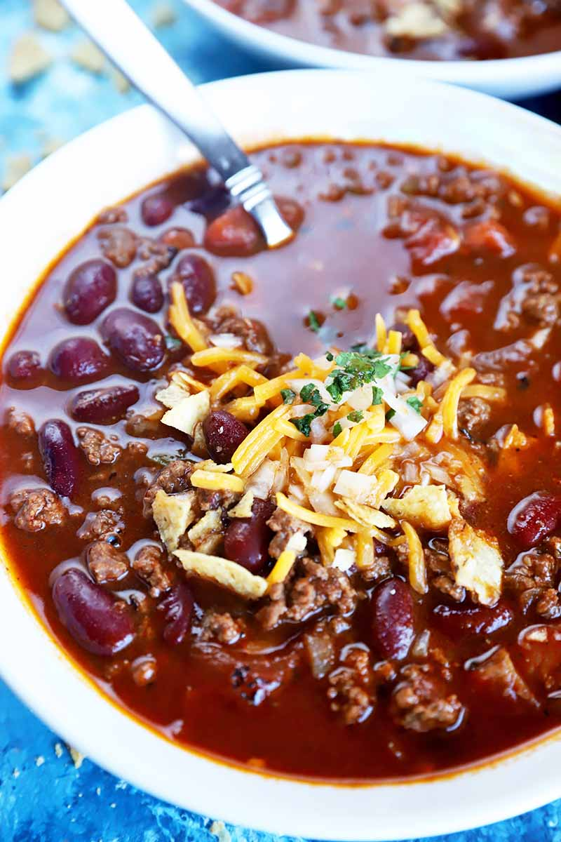 Vertical image of a thick red stew in a white bowl topped with shredded cheese and sliced scallions.