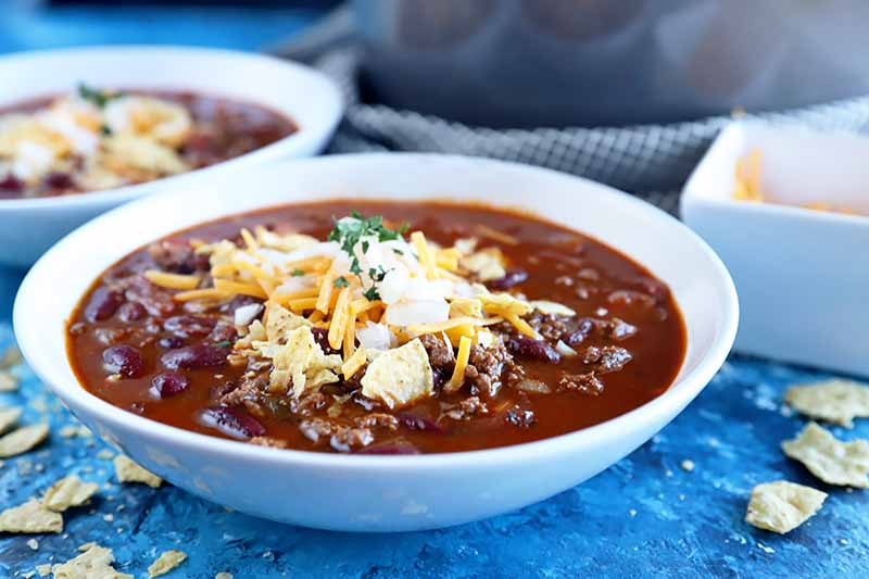Horizontal image of a bowl of stew topped with diced onions, shredded cheese, and herbs.