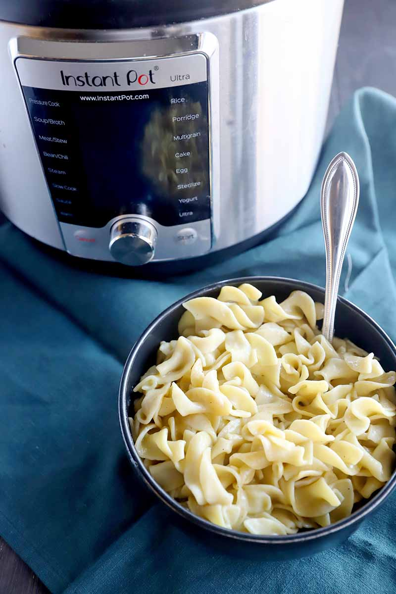 Vertical image of a bowl of pasta with a metal spoon inserted into it on top of a blue towel next to a kitchen appliance.