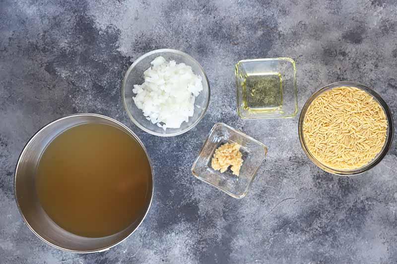 Horizontal image of a bowl of broth, chopped onion, pasta, and garlic.