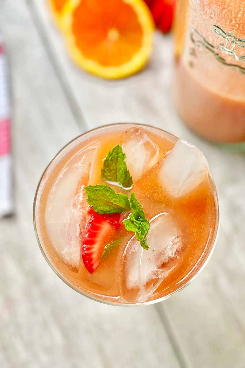 Vertical top-down image of a glass filled with a drink topped with ice cubes, fresh herbs, and sliced fruit.