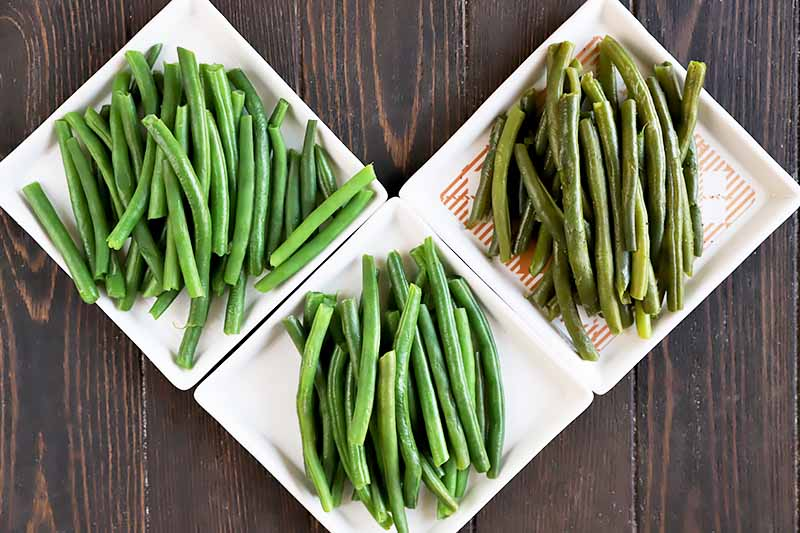 Horizontal image of three square white plates with piles of green beans made in difference methods.