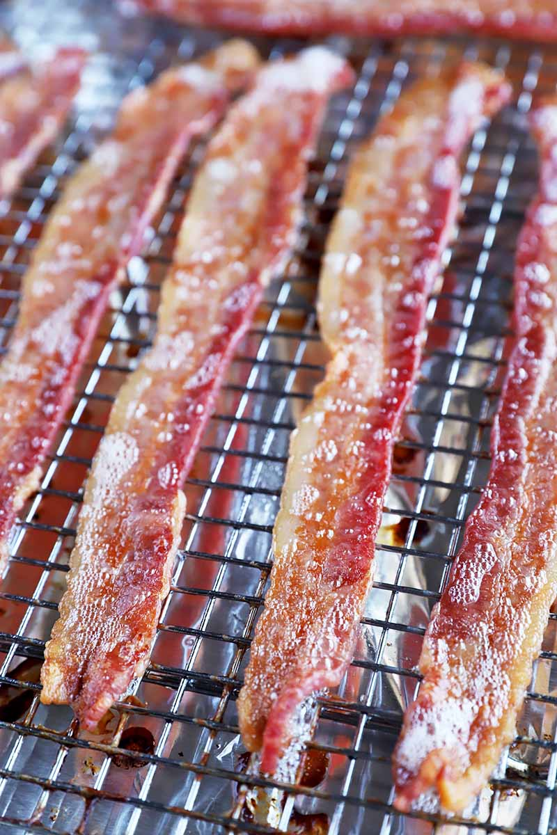 Vertical image of cooked sliced breakfast meat on a cooling rack.