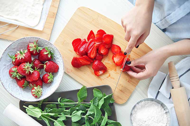 Horizontal image of a woman slicing fresh strawberries on a cutting board next to fresh mint and flour.