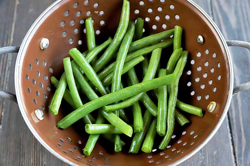 Horizontal image of raw green beans in a colander.