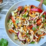 Horizontal image of a white bowl full of a colorful slaw next to slices of lemon and lime.