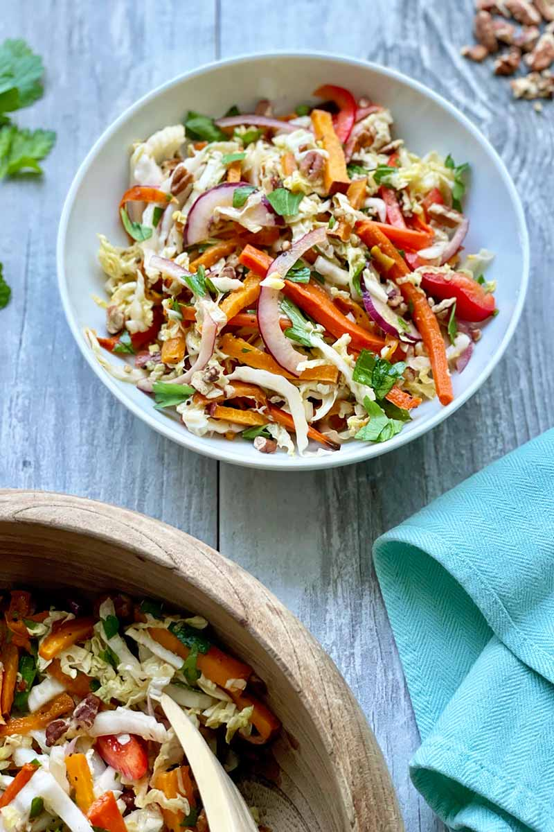 Vertical image of a white bowl and a wooden bowl filled with a mixed vegetable slaw.