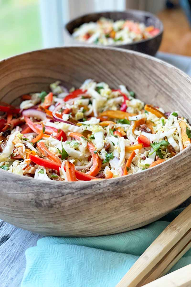 Vertical image of a wooden bowl filled with an assorted vegetable salad.