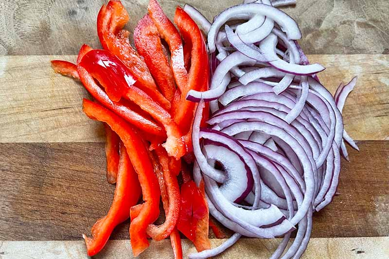 Horizontal image of slices of bell peppers and red onions.