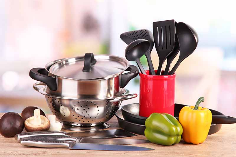 Horizontal image of various kitchen tools and bell peppers on a kitchen countertop.